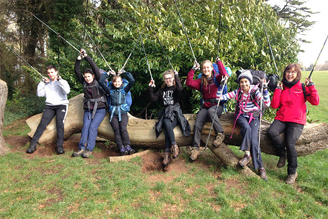 Teenage nordic walking group holding poles